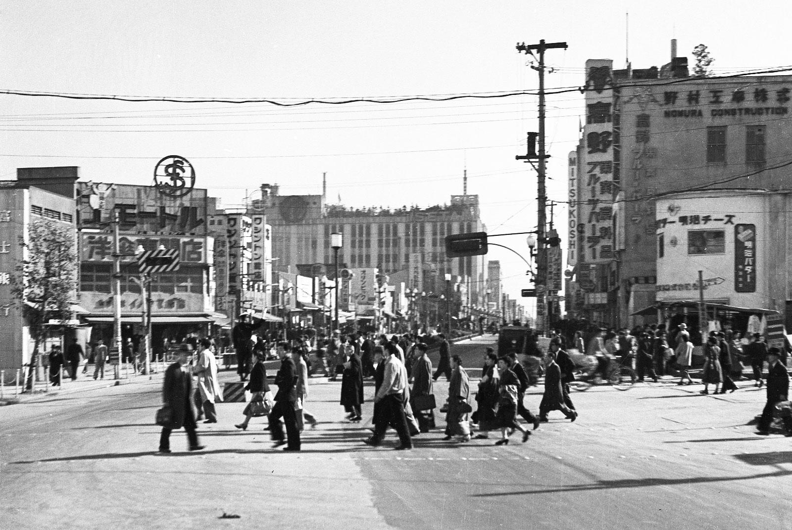 新宿駅前から見た新宿通りの様子。行き交う人々や交通整理する警察官の姿、立ち並ぶ低層の商店などが時代を物語る。昭和27年