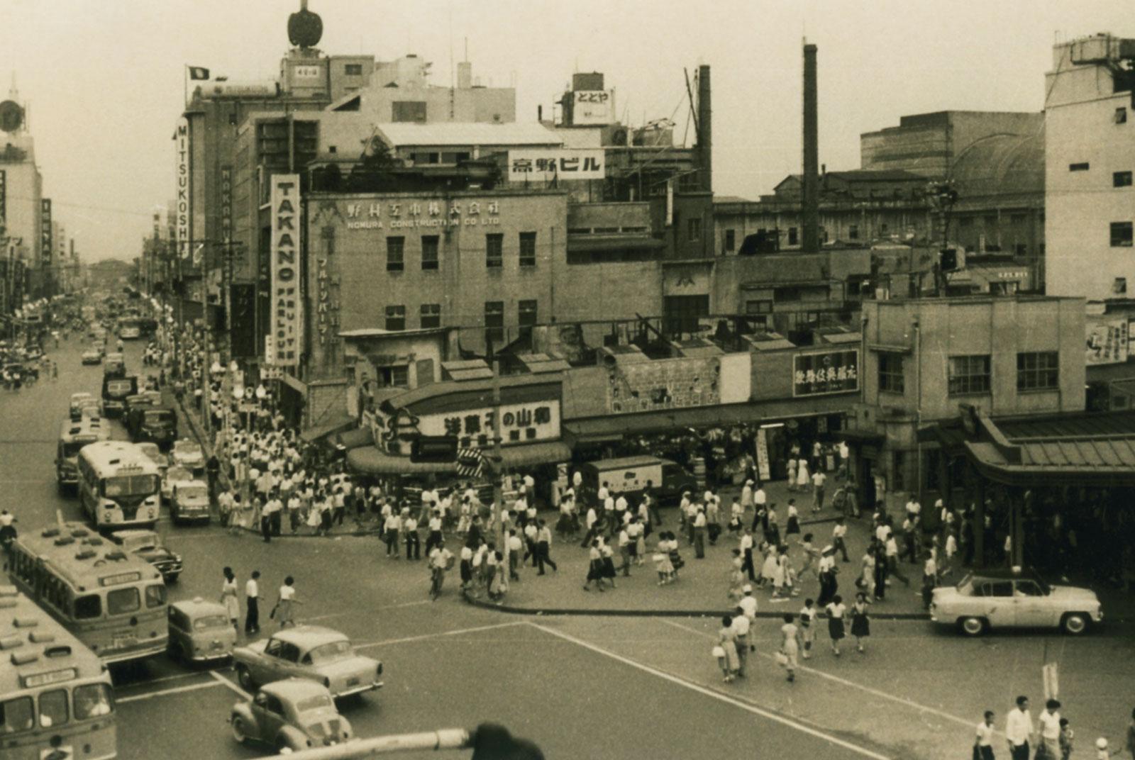 新宿駅東口前。高野ビルの手前は闇市の名残の野原組のマーケット(通称ハモニカ横丁)と、尾津喜之助が恩赦で刑務所から出所した後、昭和27年に建設した龍宮マーケット。昭和34年7月17日