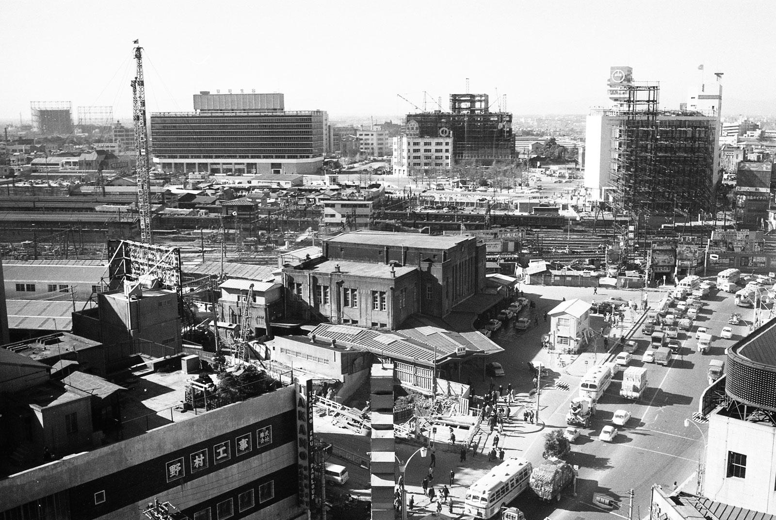 昭和37年(1962)頃の新宿駅東口の様子。 駅舎周辺で建て替え工事が始まっている。西口方面で進むビル建設の合間からは、淀橋浄水場の様子が見える