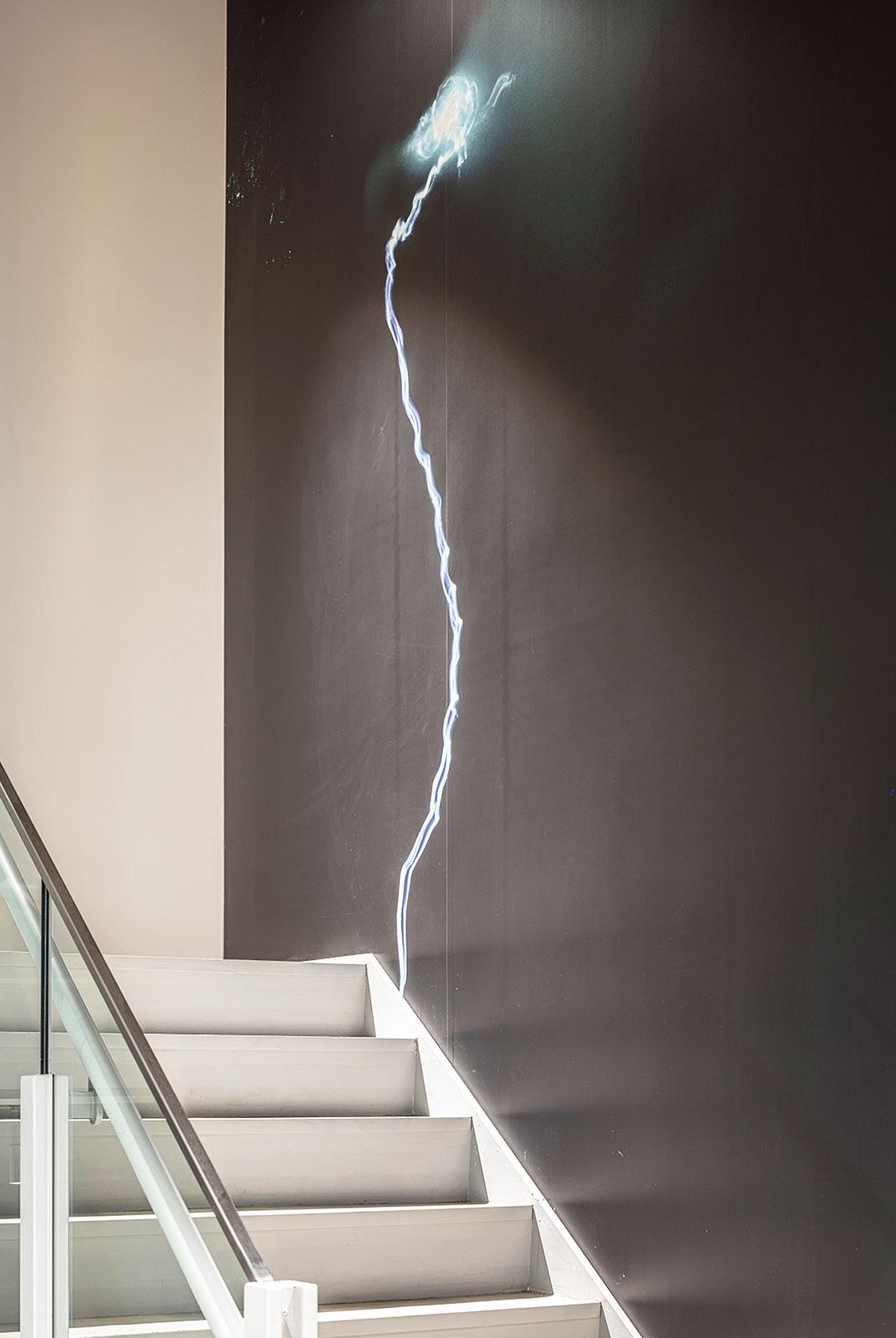 コンセプチュアルカメラマン濱田祐史さんの作品を配置した階段フォトアート。上階の壁面につながる巨大な作品。川にLEDの光を流し、川の流れを視覚化したもので空間そのものを体験してもらえたらと設置された