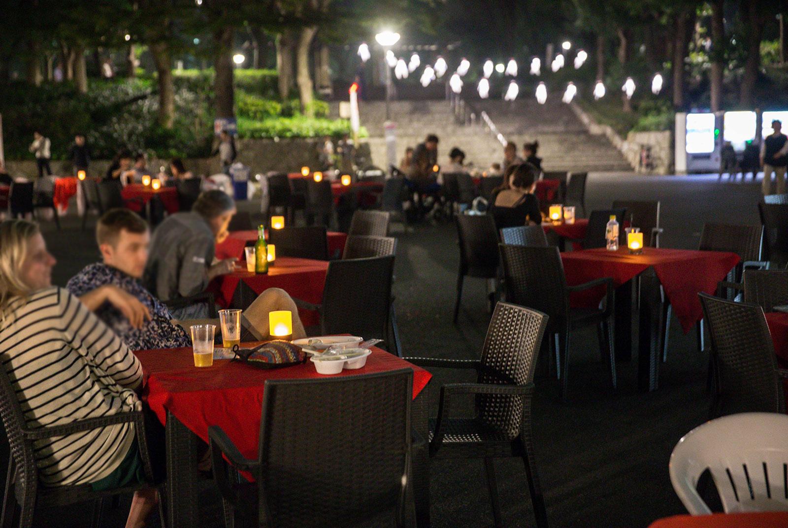 映画を観ながら、出店するキッチンカーの食事も楽しめるテーブル席。ほかに、ピクニックやフェスのように自由なスタイルを楽しめるようレジャーシートも用意した(「新宿パークシネマフェスティバル」)