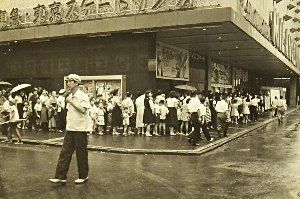 写真は1960年代の新宿東急文化会館。映画館に並ぶ人の長い列
